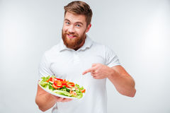 Happy bearded man pointing finger at plate with fresh salad Stock Images