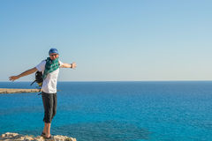 Happy bearded man on sea coast. Happy bearded man in sunglasses stands arms outstretched on a rock above the sea. Traveler on the sea coast having fun in sunny Stock Photo