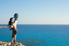 Happy bearded man on sea coast. Happy bearded man in sunglasses stands on a rock above the sea and looks into the distance. Traveler on the sea coast having fun Stock Photography