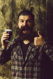 Happy bearded man showing thumbs up with blue plastic cup. Takeaway coffee. Happy bearded man or brutal caucasian hipster with grey hair, long beard and royalty free stock photo