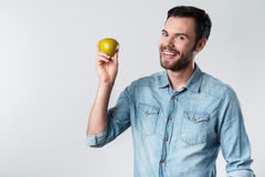 Happy bearded man smiling and holding an apple. Stock Image