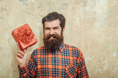 Happy bearded man smiling with red gift box with bow. Happy bearded man, caucasian hipster, with long beard and moustache in plaid shirt smiling with red gift Stock Images