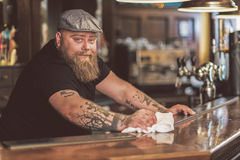 Happy bearded man standing at bar counter. Be positive. Joyful tapster cleaning work surface in pub. He looking at camera cheerfully Stock Photos