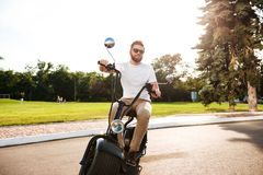 Happy bearded man in sunglasses rides on modern motorbike Royalty Free Stock Images