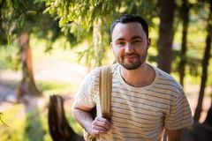 Happy bearded man traveler with backpack walking in forest. Tourism, travel, adventure, hike concept - smiling young man. Walking with backpack in woods Stock Images
