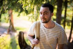 Happy bearded man traveler with backpack walking in forest. Tourism, travel, adventure, hike concept - smiling young man. Walking with backpack in woods Royalty Free Stock Photography