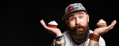 Happy bearded bald man holding two cream cakes on black background. Happy bearded man in a trendy stylish cap is holding two cream muffin cakes on a cobbler royalty free stock photo