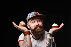 Happy bearded bald man holding two cream cakes on black background. Happy bearded man in a trendy stylish cap is holding two cream muffin cakes on a cobbler royalty free stock photos