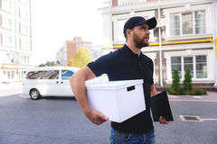 Happy bearded postman goes to client's home royalty free stock photography