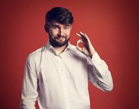Happy bearded smiling business man showing okay sign in fashion Royalty Free Stock Images