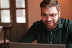 Happy bearded young man using laptop computer. Stock Photography