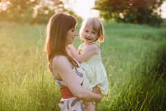 Happy beatiful Mom kisses and hugs daughter on nature in sunset light. Mom kisses and hugs daughter on nature, family, motherhood, child royalty free stock image