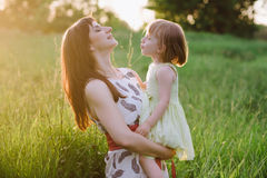 Happy beatiful Mom kisses and hugs daughter on nature in sunset light. Mom kisses and hugs daughter on nature, family, motherhood, child stock images