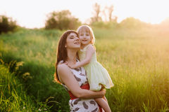Happy beatiful Mom kisses and hugs daughter on nature in sunset light. Mom kisses and hugs daughter on nature, family, motherhood, child royalty free stock photo