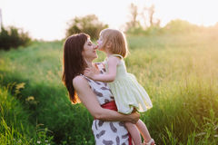 Happy beatiful Mom kisses and hugs daughter on nature in sunset light. Mom kisses and hugs daughter on nature, family, motherhood, child royalty free stock images
