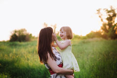 Happy beatiful Mom kisses and hugs daughter on nature in sunset light. Mom kisses and hugs daughter on nature, family, motherhood, child stock photo
