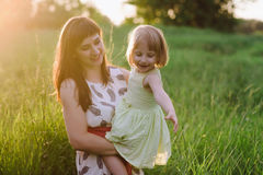 Happy beatiful Mom kisses and hugs daughter on nature in sunset light. Mom kisses and hugs daughter on nature, family, motherhood, child stock image