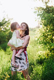 Happy beatiful Mom kisses and hugs daughter on nature in sunset light. Mom kisses and hugs daughter on nature, family, motherhood, child stock photos