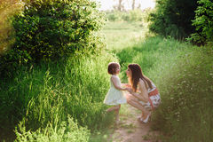 Happy beatiful Mom kisses and hugs daughter on nature in sunset light. Mom kisses and hugs daughter on nature, family, motherhood, child royalty free stock photography