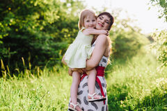 Happy beatiful Mom kisses and hugs daughter on nature in sunset light. Mom kisses and hugs daughter on nature, family, motherhood, child stock photography