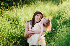 Happy beatiful Mom kisses and hugs daughter on nature in sunset light. Mom kisses and hugs daughter on nature, family, motherhood, child royalty free stock photos