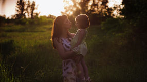 Happy beatiful Mom kisses and hugs daughter on nature in sunset light Stock Photos