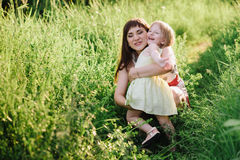 Happy beatiful Mom kisses and hugs daughter on nature in sunset light Royalty Free Stock Photo