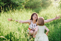Happy beatiful Mom kisses and hugs daughter on nature in sunset light Royalty Free Stock Images
