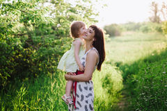 Happy beatiful Mom kisses and hugs daughter on nature in sunset light Royalty Free Stock Photos