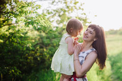 Happy beatiful Mom kisses and hugs daughter on nature in sunset light Royalty Free Stock Photography