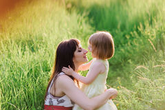 Happy beatiful Mom kisses and hugs daughter on nature in sunset light Stock Image
