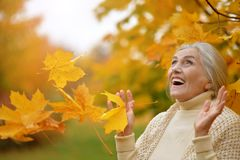 Happy beautifil elderly woman posing. In park stock photography