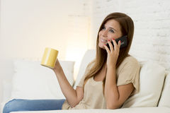 Happy beautifu woman on couch talking on mobile phone relaxed and cheerful smiling at home sofa Stock Image