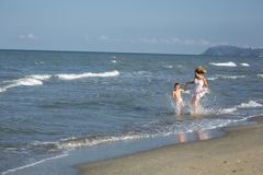 Happy beautiful mom and child running along the sea beach, copy-space Royalty Free Stock Image