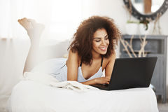 Happy beautiful african girl in sleepwear lying on bed at home smiling looking at laptop. Royalty Free Stock Image
