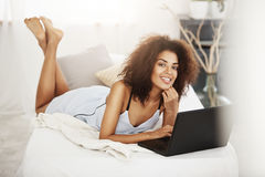 481dad9e6e96 Happy beautiful african girl in sleepwear lying with laptop on bed at home  smiling looking at