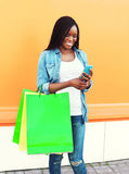 Happy beautiful african woman with shopping bags using smartphone in city. Over colorful orange background stock photography