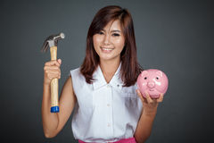 Happy Beautiful Asian girl with pink pig money box and hammer Stock Image