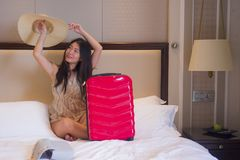 Happy and beautiful Asian Korean tourist woman with travel suitcase just arrived at five star hotel room playing on bed with Summe. Lifestyle portrait of young stock photography