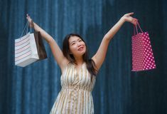 Happy and beautiful Asian Korean woman walking on the street posing on background smiling cheerful carrying shopping bags stock image