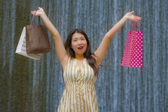 Happy and beautiful Asian Korean woman walking on the street posing on background smiling cheerful carrying shopping bags royalty free stock image