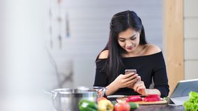 Happy beautiful Asian woman enjoying break using smartphone at home kitchen stock video