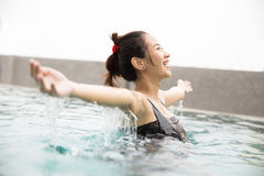 Happy beautiful asian woman enjoying time on the pool, open arms Stock Photos