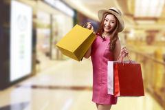 Happy beautiful asian woman with hat and shopping bags royalty free stock photos