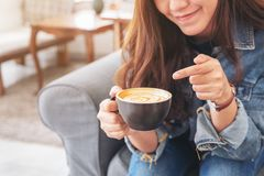 A happy beautiful asian woman holding and pointing finger at a cup of hot coffee in cafe. Closeup image of a happy beautiful asian woman holding and pointing royalty free stock photos