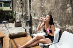 Asian woman blowing soap bubbles. Happy beautiful Asian woman relax on sofa and blow soap bubbles at old building roof top. Funny activity with copy space for Royalty Free Stock Photo