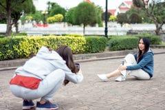 ฺBeautiful Asian woman with smartphone taking picture of her friend in an old city,lifestyle and people concept. Happy beautiful Asian women with smartphone stock images