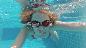 Happy beautiful attractive young woman in the swimming pool, underwater view. Action camera. Happy beautiful attractive young woman swimming in the swimming pool stock video