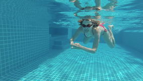 Happy beautiful attractive young woman in the swimming pool, underwater view. Action camera. Happy beautiful attractive young woman swimming in the swimming pool stock footage