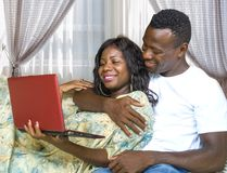 Young happy and beautiful black afro American couple in love enjoying at living room sofa couch with laptop computer networking stock photo